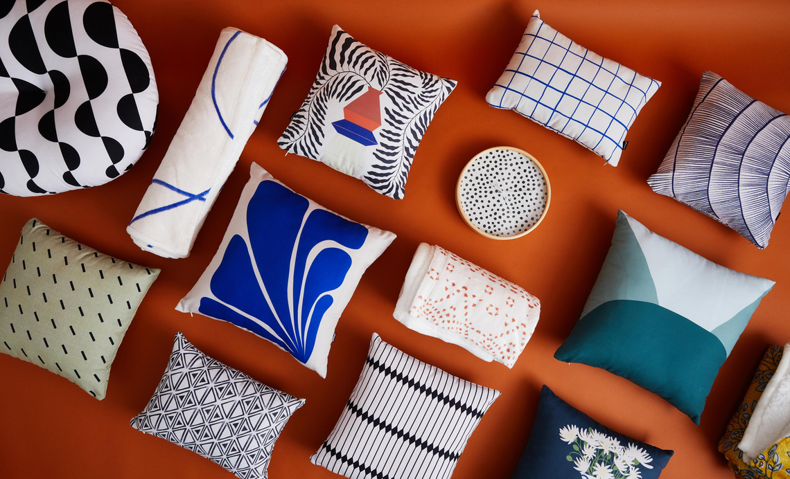pillows, blankets, and wall clocks on a rust colored background