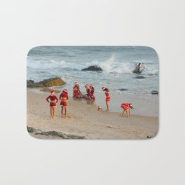 Christmas background. Happy girls in Santa Clause suit having fun on the beach. Bath Mat
