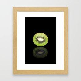 Half kiwi on a black reflective background Framed Art Print