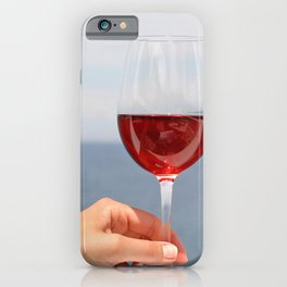 Hand with glass of wine, blue sea in background iPhone Case