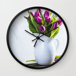 A bouquet of purple tulips in a vase against the wall Wall Clock