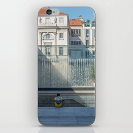 Person sitting back to back in front of a modern fountain splashing water on a huge glass window iPhone Skin