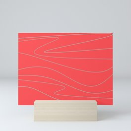 Blue curves on a red background Mini Art Print