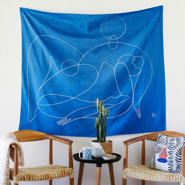 blue line drawing tapestry hanging over chairs