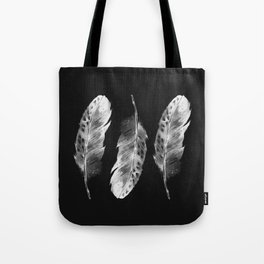 Three feathers on black background Tote Bag
