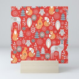 Scandinavian Christmas pattern on a red background. Deer, owls, foxes, trees and grass, snowflakes. Mini Art Print