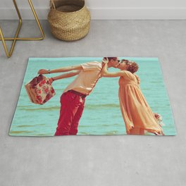 Young happy married hipsters in trendy clothes kissing on beach and holding their shoes. Couple walking on beach.  Sunny summer day. Vintage style. Romantic Rug