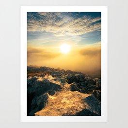 Amazing sunset above clouds and sun lit rocks Art Print