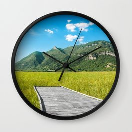 Beautiful mountain scenic with wooden footpath in field under sunlight Wall Clock