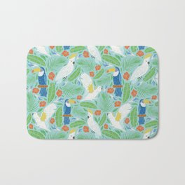 Blue toucan with white cockatoo amoung tropical flowers and leaves Bath Mat