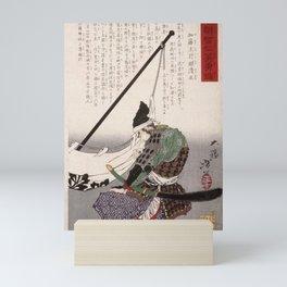 Tsukioka Yoshitoshi - A Mirror of Wisdom... (1878) - Kato Kazuenokami Kiyomasa kneeling by a banner Mini Art Print