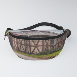 the cottage, a small house on the hill surrounded by greenery Fanny Pack