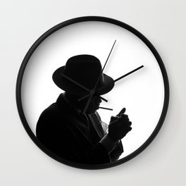 Silhouette of private detective in old fashion hat lights a cigarette Wall Clock