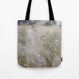 Tall wild grass growing in a meadow Tote Bag