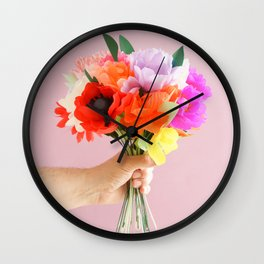 Hand holding paper flowers Wall Clock