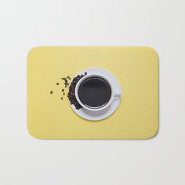 Black Cup of Coffee with Coffee Beans on Yellow Bath Mat