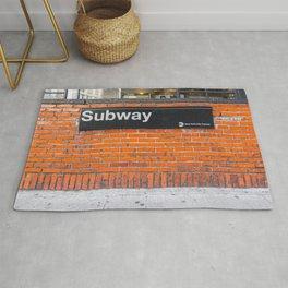 subway sign on a brick wall Rug