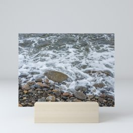 Wave washing over pebbles Mini Art Print