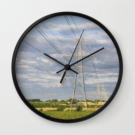 Evening light illuminating electricity pylons. Norfolk, UK. Wall Clock