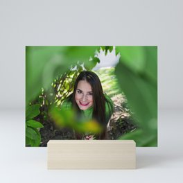 Cute young girl smiles surrounded by leaves Mini Art Print