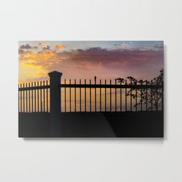 High contrast silhouette sunset scene with small bird over fence and orange and blue background Metal Print
