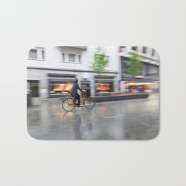 young woman on her bicycle traveling in the rain Bath Mat