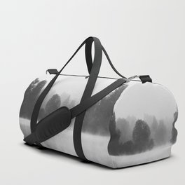 Trees disappearing in morning fog above the lake Duffle Bag