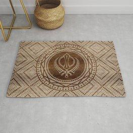 Khanda symbol on wooden texture Rug