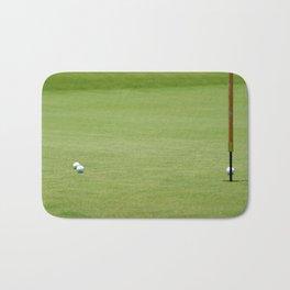 Golf balls near flagstick Bath Mat