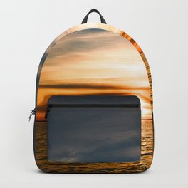 Sun glowing at sunset in the clouds of blue sky Backpack