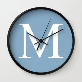Letter M sign on placid blue background Wall Clock