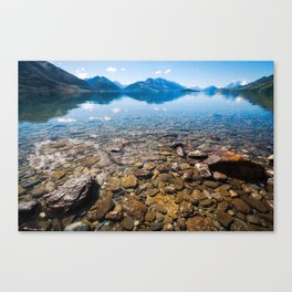 Snow-capped mountains view in summer from the rocky shore of lake Wakatipu. Canvas Print