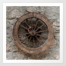 Wooden wheel hanging on a stone wall Art Print