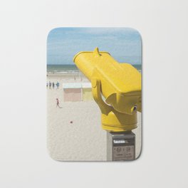 Yellow spotting scope on the beach Bath Mat