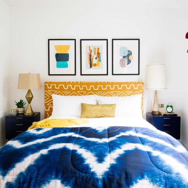 bedroom with blue comforter and framed prints