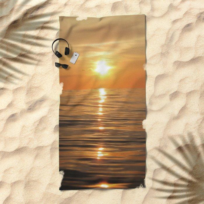 Sun setting over calm waters Beach Towel