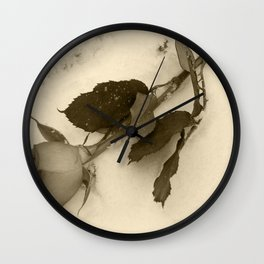 A lone rose resting in the snow Wall Clock