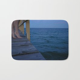 Woman standing on the edge of a pier Bath Mat