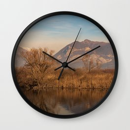 Tree in the foreground and mountains in the background are reflected in the river water Wall Clock