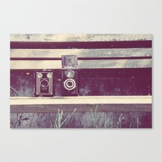 two cameras sitting on a park bench ...  Canvas Print