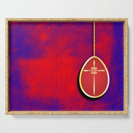 Gold cross in red egg hanging against a rich red and purple Serving Tray