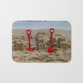sandcastles and red spades on the beach Bath Mat