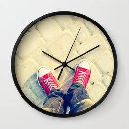 young man feet in red sneakers on cobbled road Wall Clock