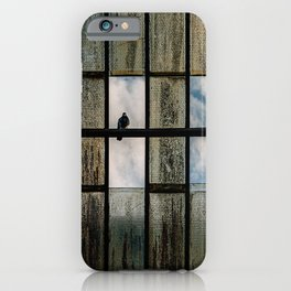 Lonely bird on a broken roof with clouds and blue sky iPhone Case