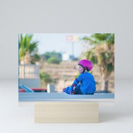 An adorable preschooler weepy because her plastic roller blades made her fall. On a city background. Mini Art Print