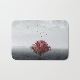 red tree in a field Bath Mat