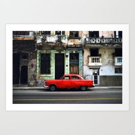 RED CAR PARKED ON ROAD IN FRONT CONCRETE BUILDING Art Print
