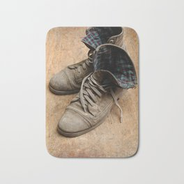 Pair of old leather shoes, worn-out and dusty, on wooden background Bath Mat