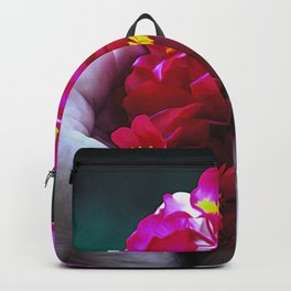 Red flowers held in hand with green background Backpack