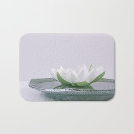 white lotus flower in a green bowl; wisteria white background Bath Mat